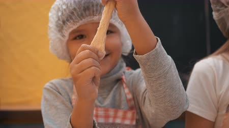 piekarz : Playful girl in disposable cap stretching dough at culinary master class. Happy girl playing with raw dough while preparing pastry at bakery class in cooking school