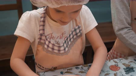 piekarz : Young girl rolling dough for italian pizza on culinary class in cooking school. Happy girl preparing round circle for pie on cooking class in bakery school. Cooking education in school
