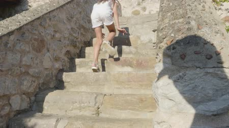szandál : Teenager girl walking up on stairs in stony fortress. Tourist girl in white clothes and sandals climbing on stony staircase