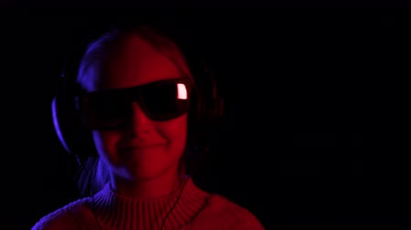 devise : Cheerful teenager girl in black sunglasses and headphones listening music in black studio. Happy girl enjoying music in earphones and dancing in dark room with red and blue lighting Stock Footage