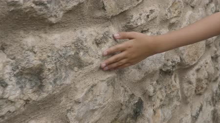 stony : Young hand touching stroke old stony wall outdoor. Close up teenager hand touching stony wall surface on old street at walk