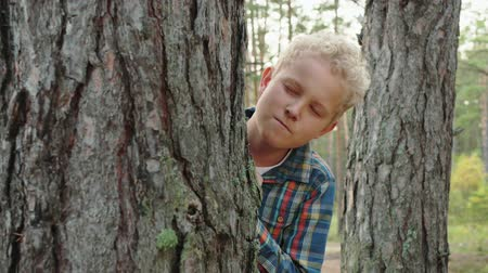 tongue out : Playful boy hiding behind tree in forest. Adorable happy teenage boy in checkered shirt playing hide and seek in forest