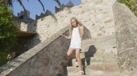 taş duvar : Girl walking down stairs on ancient castle. Low angle view of adorable teenage girl in white clothes walking down steps on ancient fortress at sunny summer day