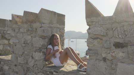 taş duvar : Happy girl sitting and dancing on stone wall. Adorable cheerful teenage girl in white clothing sitting on ruins of ancient castle near sea harbour with ships at sunny summer day