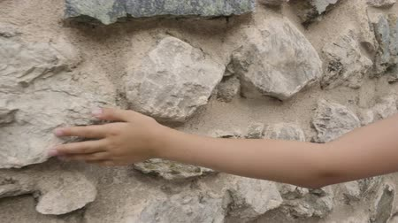 taş duvar : Cropped shot of human hand touching stone wall. Close-up partial view of child walking and touching ancient wall with palm at sunny summer day
