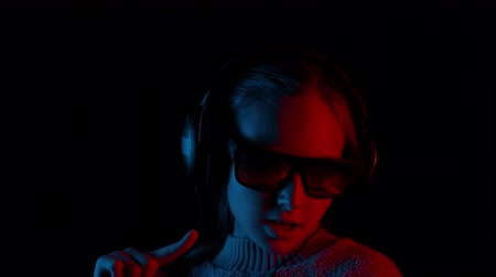 şarkı : Happy girl in headphones and sunglasses singing in darkness. Portrait of cute teenage girl in sweater, sunglasses and headphones posing and singing on black background
