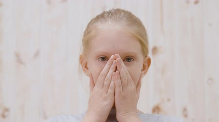 kleine meisjes : Scared girl with hands on face looking at camera. Portrait of terrified little girl hiding face behind palms and looking at camera. Fear concept Stockvideo
