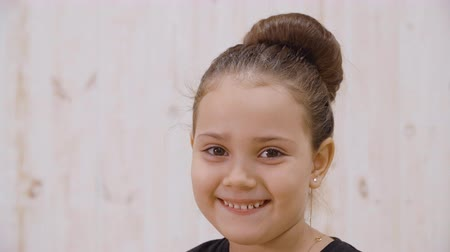 fortunate : Close-up view of adorable little girl smiling at camera. Portrait of beautiful cheerful preteen girl smiling and looking at camera Stock Footage