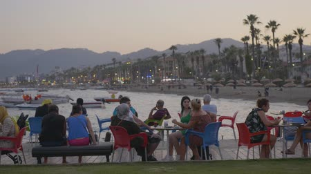 столовая гора : Marmaris, Turkey - September 23, 2019: visitors discussing in evening outdoor cafe. Tourist people sitting at table in summer cafe on sea beach on mountain landscape Стоковые видеозаписи