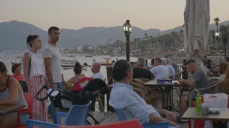 столовая гора : Marmaris, Turkey - September 23, 2019: tourist people relaxing in evening cafe on sea quay on ships landscape. Tourist people sitting in outdoor cafe on sea promenade