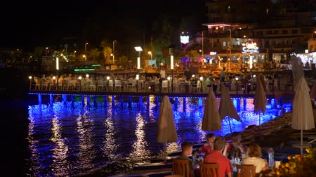 wrzesień : Marmaris, Turkey - September 23, 2019: tourist people resting in evening cafe on sea embankment. Relaxed people sitting in outdoor cafe on sea quay with blue night lighting