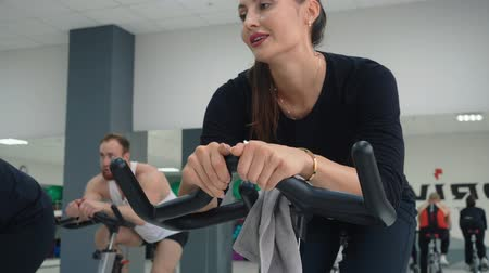 metabolismo : Young woman cycling indoor. Fitness woman training on bike machine on cycling class in gym club. Sport group training exercise on static bike in fitness club. Sport people practising cardio exercise