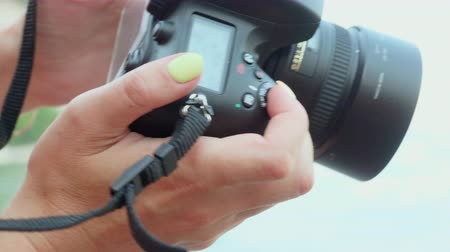 make photo : Close up woman photographer making photo by professional camera. Woman looking to camera screen while shooting photography outdoor Stock Footage