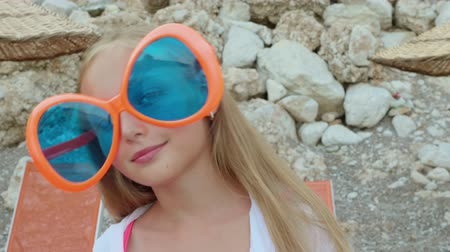 awatar : Portrait happy teenager girl in large sunglasses smiling to camera. Face funny girl swaying head in big blue sunglasses on summer beach