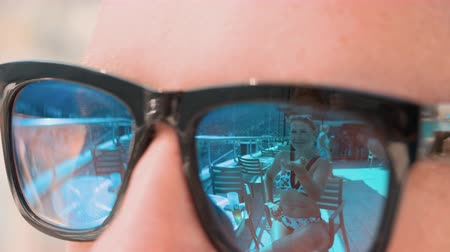 conquest : Female reflection in mirrored sunglasses close up. Flirting playful woman in bikini sending air kiss to man in mirrored sunglasses. Summer relaxing while vacation travel Stock Footage