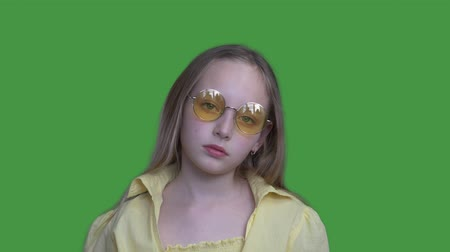 tenso : Young girl teenager in yellow glasses and yellow dress looking to camera on green background. Serious girl posing front camera on chroma key screen. Alpha channel, keyed green screen
