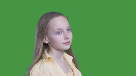 tenso : Portrait cute girl with long blond hair winding on green background. Romantic teenager girl looking away on chroma key screen in studio. Alpha channel, keyed green screen