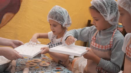 enrolado : Young girls taking flour for preparation pastry on baking class in culinary school. School girl cooking donut on cooking master class on school lesson