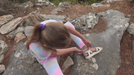 sıva : Girl applying adhesive plaster on foot while hiking in mountains. Overhead view of injured teenage girl sitting on rock and applying medical plaster on leg feet during mountain trekking
