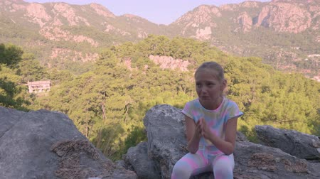 wspinaczka górska : Upset child sitting on rock and crying in mountains. Sad teenage girl sitting and crying in mountains at summertime, high angle view Wideo