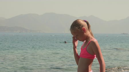 looking down : Adorable girl looking down at sea water and thinking at summertime. Cute pensive teenage girl in pink swimsuit looking down at sea waves at summer day