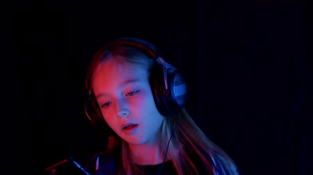 low lighting : Trendy teenager girl listening music in headphones and looking mobile. Young girl chewing gum and listening mobile music in pink red and blue neon lighting in cyberpunk studio