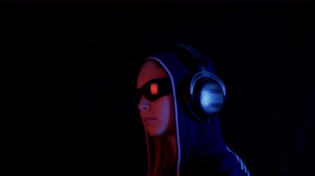 low lighting : Teenager girl in hood and headphones listening music on black studio with neon red and blue lighting. Cyberpunk girl in black glass enjoying music in earphones in dark room with neon light. Slowmo