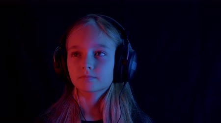 гаджет : Happy teenager relaxing in music headphones in black with red and blue neon light. Face enjoying mobile music in headphones in dark room. Slow motion girl listening music Стоковые видеозаписи