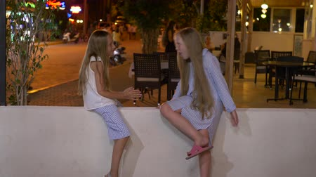 сплетни : Two happy girls talking on street in the evening. Side view of adorable teenage girls in casual clothing resting on white fence wall and chatting in city at night time Стоковые видеозаписи