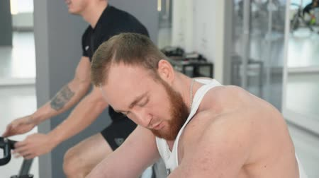 собственность : Bearded man looking at himself own muscles in cycling class. Side view of sporty muscular young men training on bikes at cycling workout in gym