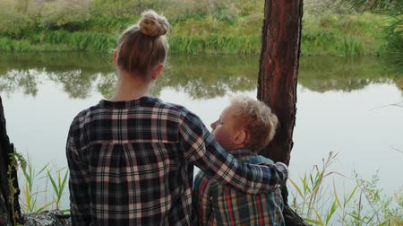 bağ : Adult sister hugging young brother on river shore in pine trees forest. Happy teenager girl and boy embracing on river coast in coniferous woodland