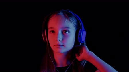 low lighting : Beautiful teenager girl listening music headphones in dark room with neon lighting. Relaxing girl enjoying music in headphones in black studio with red and blue lighting Stock Footage