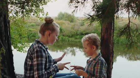 равный : Teenager girl and boy playing rock paper scissors on river shore in pine woodland. Happy sister and brother playing rock paper scissors in summer forest on river coast Стоковые видеозаписи