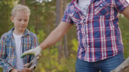 driftwood : Father and son chopping dry firewood in forest hike. Tourist dad together son teenager chopping wood with axe in summer woodland Stock Footage