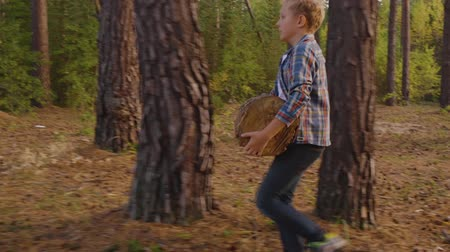 sawn : Teenager boy carrying timber log in coniferous forest. Young boy holding hard log for chopping in pine woodland Stock Footage