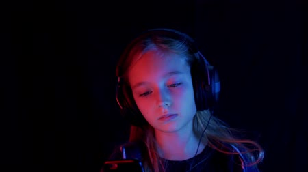 kauwgom : Girl in headphones using smartphone on black background with neon red blue light. Portrait of beautiful stylish teenage girl listening music in headphones, chewing gum using mobile phone in darkness