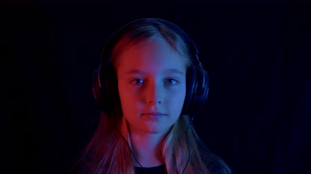 cyberpunk : Cute teenage girl in headphones listening music in darkness neon light. Portrait of beautiful teenage girl in headphones listening music, shaking head and looking at camera on black background