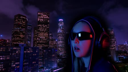 low lighting : Teenager girl in hood and black sunglasses listening headphones music neon city background. Girl teenager chewing gum wearing music earphones on night city landscape