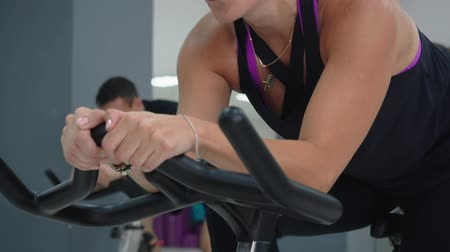 afslanken : Beautiful focused woman exercising in cycling class. Close-up view of attractive brunette concentrated woman looking away while training on spin bike