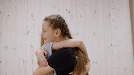 spolužák : Happy girl friends hugging on meeting on light studio background. Two girl teenager embracing while friendly meet
