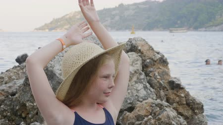 proutěný : Beautiful teenage girl in wicker hat posing on beach. Portrait of adorable happy girl in straw hat standing with raised hands near rock and looking away at sea coast during summertime