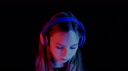 vysoká klíč : Teenage girl in headphones listening music and looking down in darkness. Neon red and blue light. Portrait of beautiful pensive teen girl listening music in headphones on black background Dostupné videozáznamy