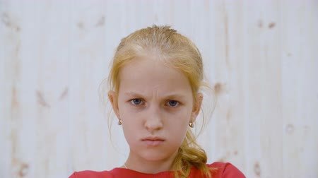 mračící : Portrait of serious teenage girl looking at camera. Close-up view of beautiful angry teen girl frowning eyebrows and looking at camera