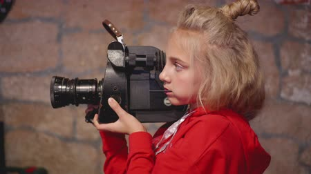 atirar : Young girl cinematographer using retro camcorder for shooting video in brick studio. Teenager girl shooting movie with videocamera on brick background