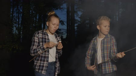 костер : Teenagers eating marshmallows from wooden sticks in forest hike near fire with smoke. Girl and boy teenagers eating marshmallows forest picnic in summer holiday