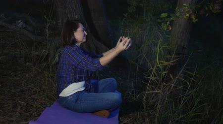 リラックスした : Relaxed woman meditating on fitness carpet in evening forest. Yoga woman relaxing in lotus pose on evening meditation on forest grass