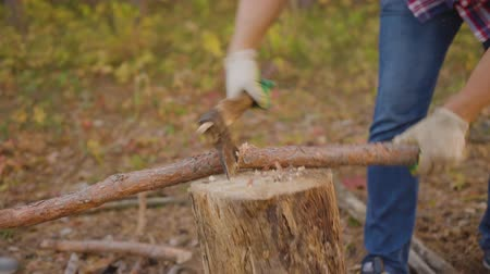 machado : Close-up partial view of man chopping wood with axe. Cropped shot of middle aged man in checkered shirt holding axe and chopping firewood