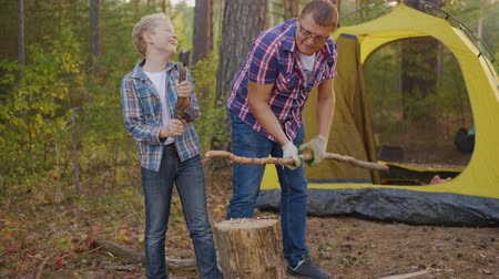 machado : Father and son chopping wood in camping. Middle aged father holding log and looking at teenage son holding axe and chopping firewood near tent in forest