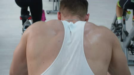 afslanken : Rear view of sweaty athletic man training on indoor bike. Back view of sweaty muscular bearded man in sportswear exercising on spin bike in cycling class Stockvideo