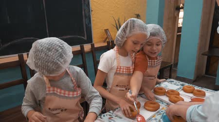 rolled : Children preparing donuts on cooking master class in culinary school. Teenagers cooking donuts in bakery school together chef cook. Culinary education Stock Footage